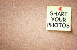Sticky pined to cork board with the phrase share your photos. Room for text Stock Image