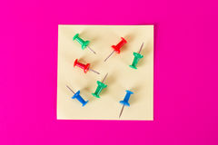 Sticky Post with Push Pins on Pink Background. Yellow sticky post with colorful push pins on pink background Stock Images