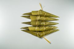 Sticky rice in bamboo grass leaf, shape look like buffalo head which is known as Kao Tom Kao Kway. Sticky rice in bamboo grass leaf, shape look like buffalo stock photo