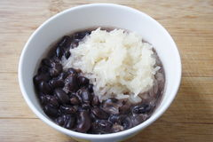 Sticky rice and black beans with coconut milk on wooden background, Thai dessert Stock Photos