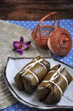 Sticky Rice Filled with Banana put on White Plate. Thai dessert sticky rice filled with banana and wrapped with banana leaf put on white plate stock images