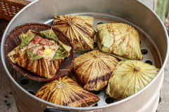 Sticky rice wrapped in lotus leaf or Zongzi is traditional Chinese food is made with sticky rice. And pork, sausage, mushrooms, nuts, ginkgo wrapped in to lotus Stock Images