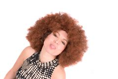 Sticky tongue. Woman with red afro wig sticking out her tongue stock images