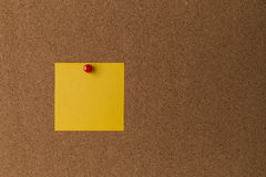 Sticky yellow note on cork board close up Royalty Free Stock Image