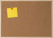 Sticky yellow note on wooden frame cork board Stock Image