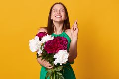 Stidio shot of pretty Caucasion woman raises crossed fingers, prays for good luck, has pleased and happy expression, wears green. Sundressr, holds white and stock photo