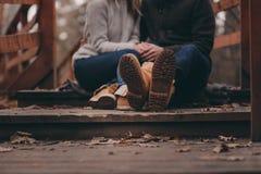 Stiefel des jungen Paargehens im Freien auf Holzbrücke im Herbst Lizenzfreies Stockfoto