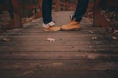 Stiefel des jungen Paargehens im Freien auf Holzbrücke im Herbst Lizenzfreie Stockbilder