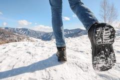 Stiefel, die zu den Winterbergen gehen Stockfotografie