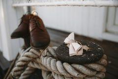 Stiefel und Bindungsschmetterlingsbräutigam auf den Schiffspollern eingewickelt im starken Jutefaserseil stockfotos