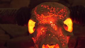 Stierenschedel met hoornen en rood licht van binnenuit het hangen op steenmuur voor binnenlands ontwerp Decoratieve de jachttrofe stock footage