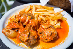 Stifado with fries on the plate Royalty Free Stock Photos