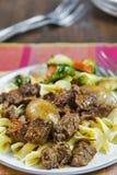Stifado griego de la carne de vaca con los tallarines de huevo y las verduras asadas Foto de archivo
