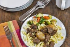 Stifado griego de la carne de vaca con los tallarines de huevo y las verduras asadas Fotos de archivo libres de regalías