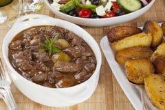 Stifado mit griechischen Salat-und Grieche-Braten-Kartoffeln stockbild