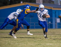 Stiff Arm The Defender. Anderson, California, USA-September 4, 2015 A running back from Orland (34) stiff arms a defender as he attempts to tackle him during an Royalty Free Stock Photo