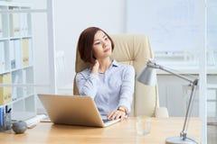 Stiff neck. Asian young female entrepreneur having stiff neck Royalty Free Stock Photos