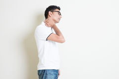 Stiff neck. Portrait of Indian guy neck pain, massaging with hand. Asian man standing on plain background with shadow and copy space. Handsome male model Stock Image