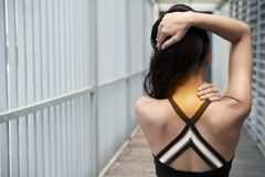 Stiff neck. Rear view of woman suffering from stiff neck Stock Image
