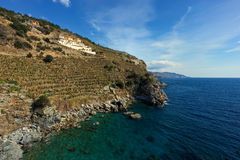 Stiff slopes of mountains descending into sea. With three villas overlooking seascape shot on sunny day Stock Image