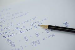 Stift über einem Blatt Papier mit Matheformeln Lizenzfreie Stockfotografie