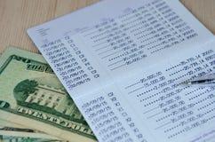Stift auf Bankkontosparbuch mit Dollarbanknote, selektives foc Stockfoto