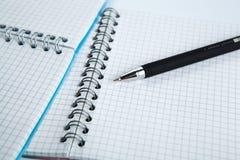Stift auf dem karierten Papiernotizbuch Stockbilder