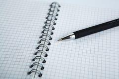 Stift auf dem karierten Papiernotizbuch Lizenzfreies Stockfoto