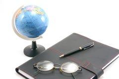 Stift auf einem Notizbuch und einer Kugel auf weißem Hintergrund Lizenzfreies Stockfoto