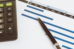 Stift auf Monatsdiagramm und Diagramm mit schwarzem Taschenrechner auf Bürotisch mit als Firma Gewinn- und Verlust-, finanziell u lizenzfreie stockfotografie