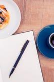 Stift auf Notizblock durch Lebensmittel und Kaffee bei Tisch Stockfotografie