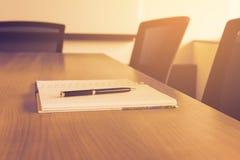 Stift auf Notizblock für Tagesordnung hielt auf Tabelle im Unternehmenskonferenzsaal stockfotografie