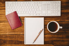 Stift auf Notizblock nahe bei Tasse Kaffee-Pass und -tastatur Stockfotos
