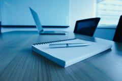 Stift auf Notizblock und Laptop und für Tagesordnung hielt auf Tabelle im leeren Unternehmenskonferenzsaal stockfoto