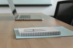 Stift auf Notizblock und Laptop und für Tagesordnung hielt auf Tabelle im leeren Unternehmenskonferenzsaal stockfotos