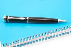 Stift auf Notizbuch Stockbild