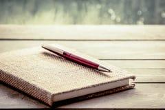 Stift auf Notizbuch auf Holztisch im regnerischer Tagesfensterhintergrund Stockfotos