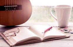 Stift auf offenem Notizbuch auf Gitarre und Kaffeetasse Lizenzfreie Stockfotografie