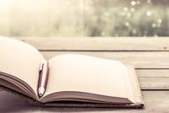 Stift auf offenem Notizbuch auf Holztisch Lizenzfreie Stockfotos