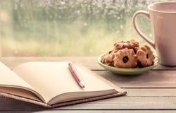 Stift auf offenem Notizbuch mit Plätzchen und Kaffeetasse Stockfotografie