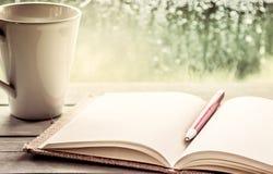 Stift auf offenem Notizbuch und Kaffeetasse Lizenzfreie Stockfotografie