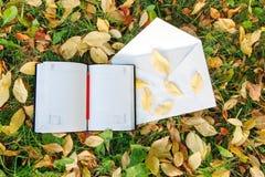 Stift, der auf dem Notizbuch mit Herbstlaub sitzt Stockbilder