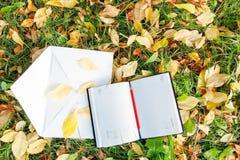 Stift, der auf dem Notizbuch mit Herbstlaub sitzt Stockbild