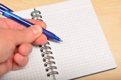 Stift in der Hand, schreibend in Tagebuch Stockfotografie