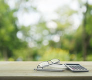 Stift, Gläser, Notizbuch und Taschenrechner auf Holztisch über Grün Lizenzfreie Stockfotos