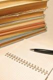 Stift, Notizbuch und alte Bücher Lizenzfreie Stockfotos