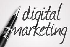 Stift schreibt digitales Marketing auf Papier Lizenzfreies Stockfoto