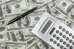 Stift, Taschenrechner und Dollar Nahaufnahme. Stockbilder