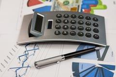 Stift, Taschenrechner und Dollar sind auf den Diagrammen Lizenzfreie Stockfotografie