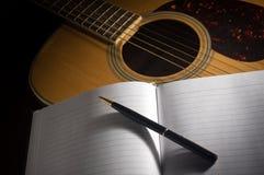 Stift und Buch auf Akustikgitarre Lizenzfreie Stockfotos
